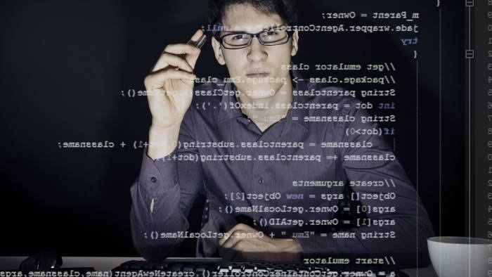 young man with glasses sitting in front of his computer, programming. the code he is working on can be seen through the screen.