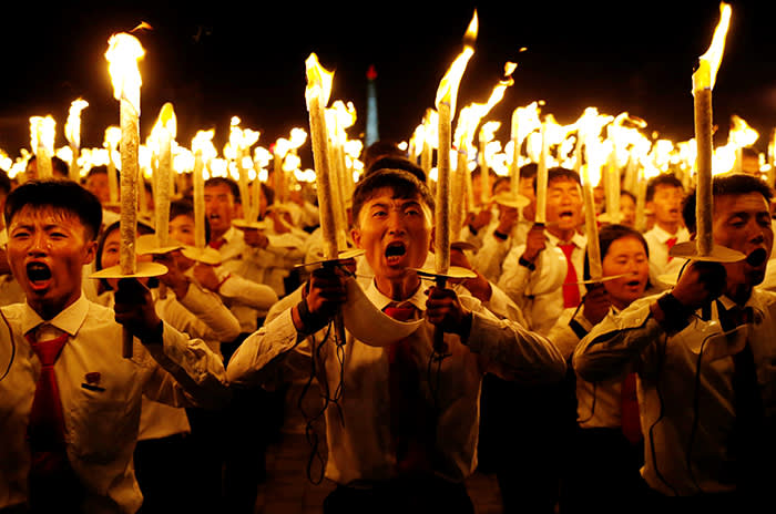 Participants shout slogans as they carry torches during a torchlight procession during the celebration marking the 70th anniversary of North Korea's foundation in Pyongyang, North Korea, September 10, 2018. REUTERS/Danish Siddiqui