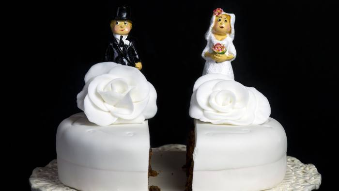A wedding cake cut in two symbolizing divorce