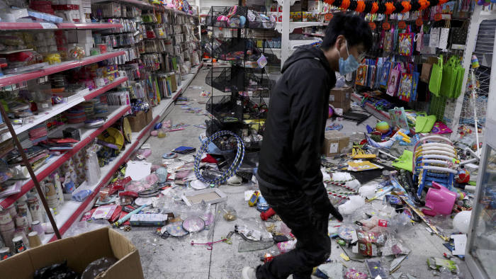 A worker cleans up a supermarket looted during protests in Santiago, Chile, Sunday, Oct. 20, 2019. Chilean President Sebastián Piñera on Saturday announced the suspension of a subway fare hike that had prompted violent student protests, less than a day after he declared a state of emergency amid rioting and commuter chaos in the capital. (AP Photo/Esteban Felix)