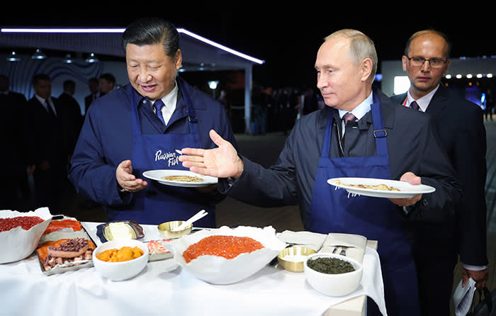 Russian President Vladimir Putin and his Chinese counterpart Xi Jinping taste pancakes while visiting