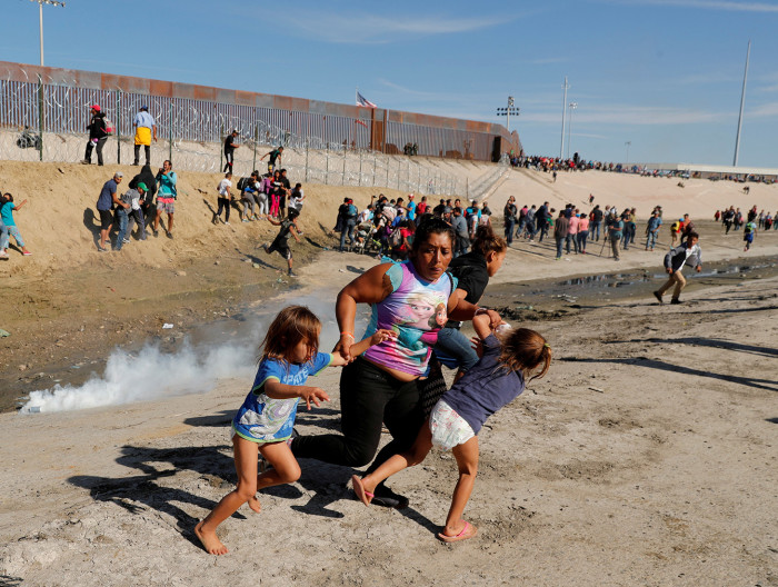 FILE PHOTO: A migrant family, part of a caravan of thousands traveling from Central America en route to the United States, run away from tear gas in front of the border wall between the U.S and Mexico in Tijuana, Mexico November 25, 2018. Reuters photographer Kim Kyung-Hoon: REUTERS/Kim Kyung-Hoon/File Photo