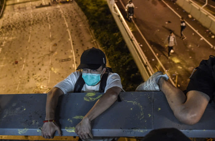 A protester lowers himself down from a bridge to a highway, to escape from Hong Kong Polytechnic University campus and from police, in Hung Hom district in Hong Kong on November 18, 2019. - Dozens of Hong Kong protesters escaped a two-day police siege at a campus late November 18 by shimmying down a rope from a bridge to awaiting motorbikes in a dramatic and perilous breakout that followed a renewed warning by Beijing of a possible intervention to end the crisis engulfing the city. (Photo by Ye Aung Thu / AFP) (Photo by YE AUNG THU/AFP via Getty Images)