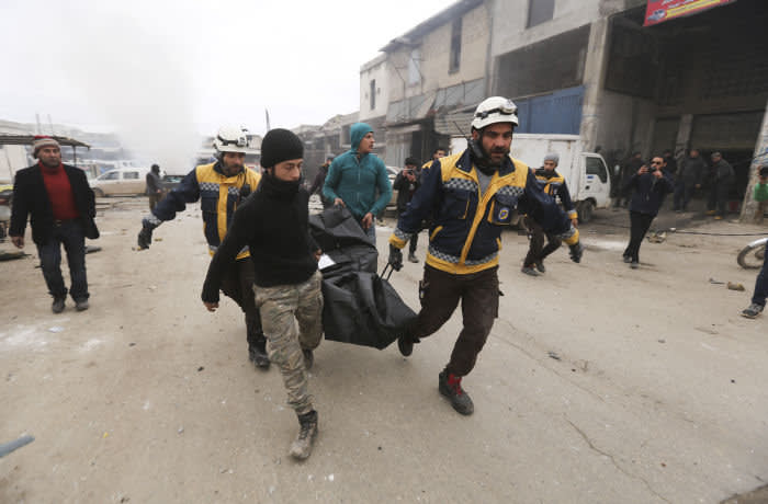 Emergency services carry a body of a person killed in a government airstrike in the city of Idlib, Syria, Tuesday, Feb. 11, 2020. The latest violence in Idlib came as government forces came closer to capturing the last rebel-held part of a strategic highway linking southern and northern Syria, which would bring the road under Syrian President Bashar Assad's full control for the first time since 2012. (AP Photo/Ghaith Alsayed)