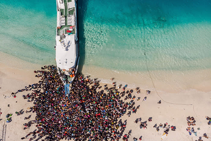 "This handout aerial photo taken by Melissa Delport from @trufflejournal on August 6, 2018 and received on August 8 shows people crowding the beach as they wait to be evacuated from Gili Trawangan island to neighbouring Lombok island a day after a 6.9 magnitude earthquake struck the area. More than 70,000 people left homeless by a deadly earthquake on the Indonesian island of Lombok were sleeping in makeshift shelters and lack food, medicine and clean water, officials said on August 8. / AFP PHOTO / @trufflejournal / Melissa DELPORT / -----EDITORS NOTE --- RESTRICTED TO EDITORIAL USE - MANDATORY CREDIT ""AFP PHOTO / Melissa Delport / @trufflejournal"" - NO MARKETING - NO ADVERTISING CAMPAIGNS - DISTRIBUTED AS A SERVICE TO CLIENTS - NO ARCHIVES -- ONE TIME USE --MELISSA DELPORT/AFP/Getty Images"