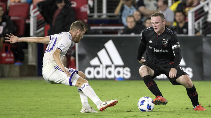 WASHINGTON, DC - AUGUST 12: D.C. United forward Wayne Rooney (9) dribbles past Orlando City midfielder Oriol Rosell (20) during a MLS match between D.C. United and Orland City SC on August 12, 2018, at Audi Field, in Washington, D.C. United defeated Orlando 3-2.  (Photo by Tony Quinn/Icon Sportswire via Getty Images)