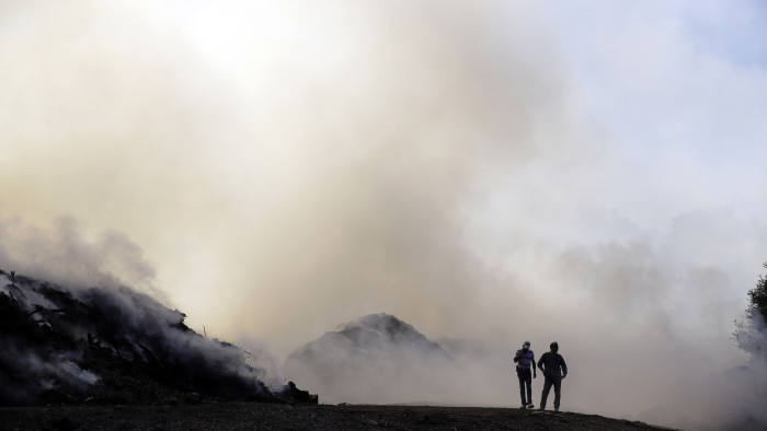 Two men walks along a dirt road as smoke from a wildfire fills the air Saturday, Oct. 12, 2019, in Newhall, Calif. The region has been on high alert as notoriously powerful Santa Ana winds brought dry desert air to a desiccated landscape that only needed a spark to erupt. Fire officials have warned that they expect more intense and devastating California wildfires due, in part, to climate change. (AP Photo/Marcio Jose Sanchez)