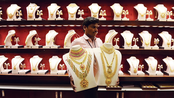 """An Indian sales assistant arranges gold ornaments during the Hindu festival of """"Akshaya Tritiya"""" at a jewellery shop in Chennai on May 7, 2019. - """"Akshaya Tritiya"""" is considered to be an auspicious day in the Hindu calendar to buy valuables and people generally flock to buy gold on this day in the belief that it will increase their wealth. (Photo by ARUN SANKAR / AFP) (Photo credit should read ARUN SANKAR/AFP via Getty Images)"""