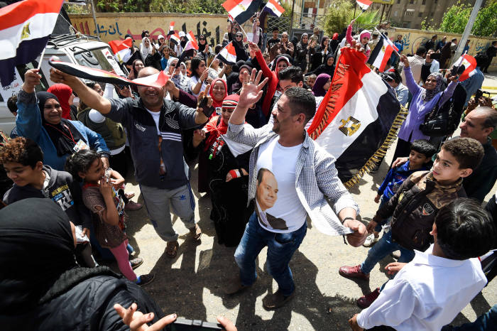 Egyptians dance and celebrate with national flags as some wear t-shirts depicting incumbent President Abdel Fattah al-Sisi, outside a polling station in al-Omraniya neighbourhood in the capital Cairo's southwestern Giza district on the first day of the 2018 presidential elections on March 26, 2018. Egyptians head to the polls in a three-day vote to choose between incumbent Abdel Fattah al-Sisi and little-known candidate Moussa Mostafa Moussa, who has struggled to make the case he is not Sisi's minion. / AFP PHOTO / MOHAMED EL-SHAHEDMOHAMED EL-SHAHED/AFP/Getty Images
