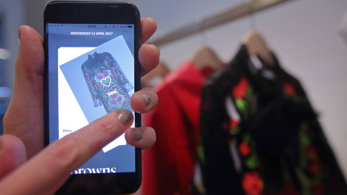 """An employee demonstrates the use of a smartphone app linked to fashion products at the launch of the Farfetch U.K. Ltd. """"Store of the Future"""" pop-up exhibition, at the Design Museum in London, U.K., on Wednesday, April 12, 2017. Thanks to a partnership with London-based fashion technology company Farfetch, you can soon get Gucci clothing and accessories whisked to your door within 90 minutes. Photographer: Luke MacGregor/Bloomberg"""