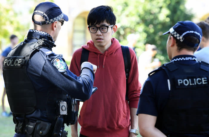 epa07749408 A man (C) is questioned by police during a protest at the University of Queensland in Brisbane, Australia, 31 July 2019. Hundreds have gathered to protest against funding agreements between Australian universities and Chinese government funded education organizations in Queensland. EPA-EFE/DAVE HUNT AUSTRALIA AND NEW ZEALAND OUT