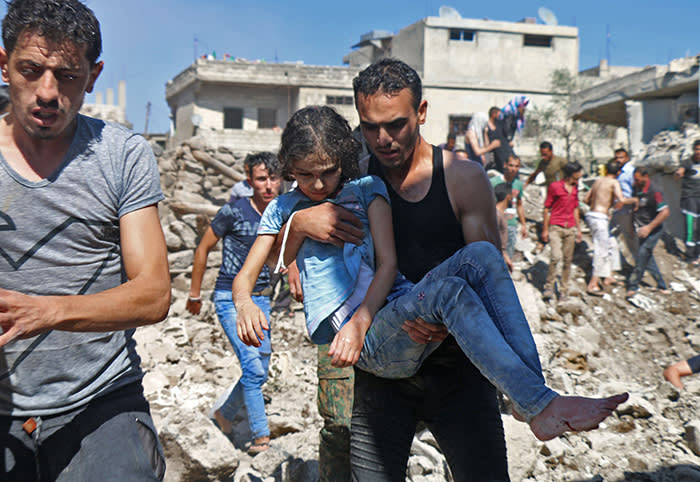 TOPSHOT - A man carries a child rescued from rubble after Syrian regime and Russian air strikes in the rebel-held town of Nawa, about 30 kilometres north of Daraa in southern Syria on June 26, 2018. Syria's army launched an assault on the flashpoint southern city of Daraa Tuesday, state media said, after a week of deadly bombardment on the nearby countryside caused mass displacement. / AFP PHOTO / Ahmad al-MsalamAHMAD AL-MSALAM/AFP/Getty Images
