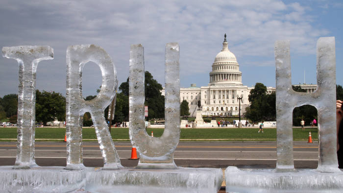 """An ice sculpture is seen spelling out the word """"truth"""" by artist duo Ligorano Reese, with the US Capitol in the background, in Washington, DC on September 22, 2018. - A poetic protest at the caustic state of politics in the era of """"fake news"""" under President Donald Trump, """"Truth Be Told"""" is the sixth sculpture in the Melted Away series launched in 2006 by Marshall Reese and Nora Ligorano, who are both 62 years old and have collaborated on art projects for nearly four decades. (Photo by Olivia HAMPTON / AFP) / RESTRICTED TO EDITORIAL USE - MANDATORY MENTION OF THE ARTIST UPON PUBLICATION - TO ILLUSTRATE THE EVENT AS SPECIFIED IN THE CAPTION (Photo credit should read OLIVIA HAMPTON/AFP/Getty Images)"""