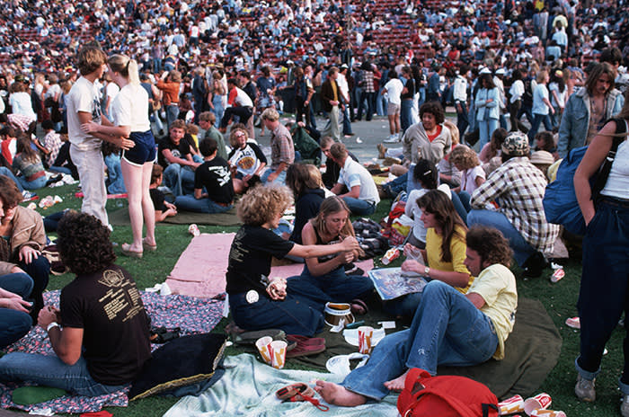 A group of spectators at California World Music Festival at the Los Angeles Memorial Stadium pass a pipe on the floor. (Photo by Henry Diltz/Corbis via Getty Images)