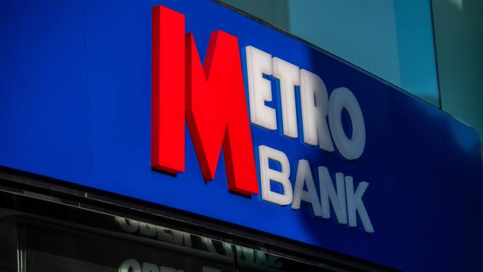 The Metro Bank logo sits on a Metro Bank Plc branch in the City of London, U.K., on Wednesday, Feb. 27, 2019. Metro Bank, the lender founded by U.S. entrepreneurVernon Hill, plunged to a record low after it disclosed that British regulators are probing how it misclassified assets, an incident that prompted a share sale. Photographer: Chris J. Ratcliffe/Bloomberg