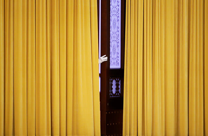 A member of staff appears from behind curtains before the visit of British Prime Minister Theresa May at the Great Hall of the People in Beijing, China January 31, 2018. REUTERS/Jason Lee TPX IMAGES OF THE DAY