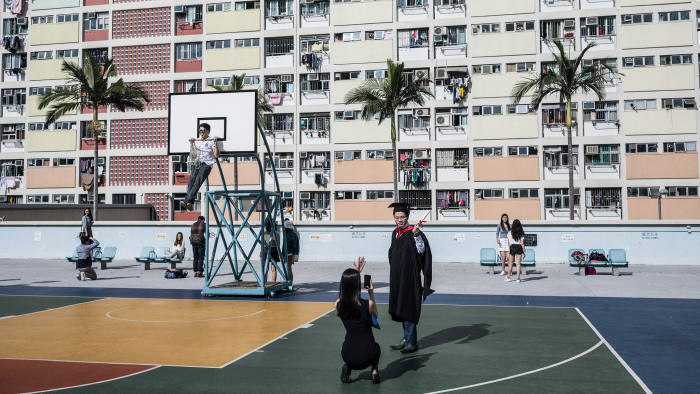 A student graduate poses for a photograph as a man hangs from a basketball hoop in front of residential homes at a public housing estate in Hong Kong on April 1, 2017. / AFP PHOTO / DALE DE LA REY (Photo credit should read DALE DE LA REY/AFP/Getty Images)
