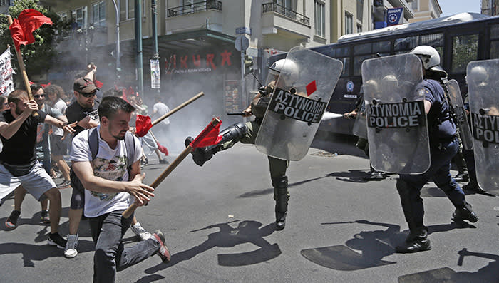 epa06772807 Protesters clash with riot police during a rally in central Athens, Greece, 30 May 2018. Greece's largest private and public sector unions General Confederation of Greek Workers (GSEE) and the civil servants' union federation ADEDY participate in a 24-hour general strike and 'Nationwide Action Day', against a new wave of austerity measures affecting pensions and salaries. The unions are demanding the immediate abolition of 'all anti-labour memorandum policies that violently and undemocratically attack labour and trade union rights'. EPA/YANNIS KOLESIDIS
