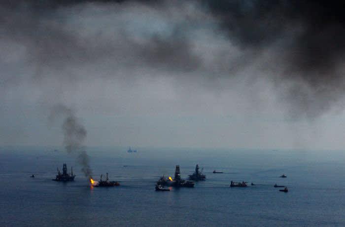 El humo de las quemaduras controladas de petróleo en la superficie del agua cuelga en el aire mientras el Perforador de desarrollo II y III trabaja en pozos de alivio y el Discoverer Enterprise y Q4000 recolectan y queman petróleo y gas en el sitio del derrame de petróleo de BP Plc Deepwater Horizon en el Golfo de México, en la costa de Luisiana, EE. UU., el sábado 19 de junio de 2010. El derrame de petróleo de BP Plc, que comenzó cuando explotó la plataforma petrolera Transocean Deepwater Horizon alquilada el 20 de abril, arroja hasta 60,000 barriles de petróleo al día en el Golfo de México, dijo el gobierno. Fotógrafo: Derick E. Hingle / Bloomberg