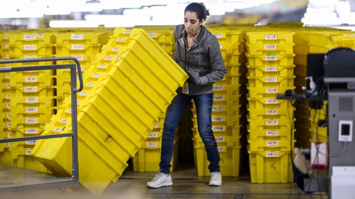 A woman works at a distrubiton station at the 855,000-square-foot Amazon fulfillment center in Staten Island, one of the five boroughs of New York City, on February 5, 2019. - Inside a huge warehouse on Staten Island thousands of robots are busy distributing thousands of items sold by the giant of online sales, Amazon. (Photo by Johannes EISELE / AFP) (Photo credit should read JOHANNES EISELE/AFP/Getty Images)