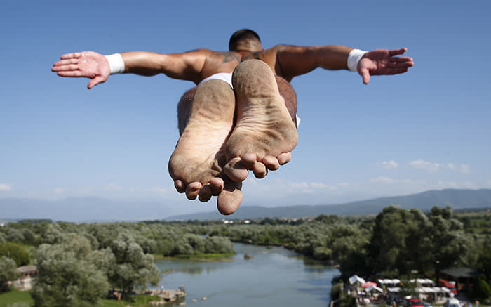 Spectators watch as diver Florid Gashi, winner of the competition, performs the winning jump from the Ura e Fshejte bridge during the 68th traditional annual high diving competition, near the town of Gjakova, Kosovo on Sunday, July 22, 2018 . (AP Photo/Visar Kryeziu)