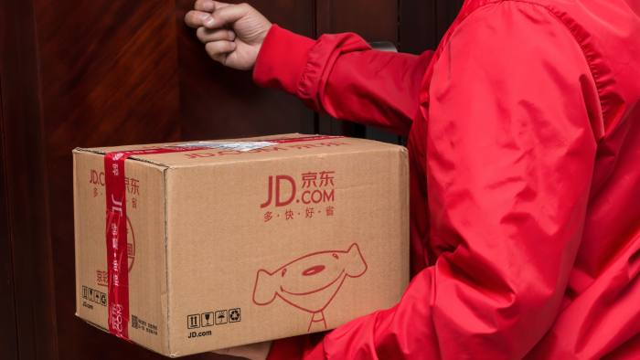 KG8MJE Zhongshan,China-November 3,2017:male courier from JD.com delivering a parcel and knocking the door.Nov 11 is the shopping day in China and many online