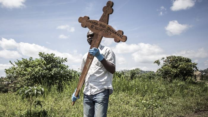 Funeral of Sister-in-law of Hussein Wabuzi - A family member of a deceased Ebola victim carries the cross before the safe burial starts on July 14, 2019 in Beni.