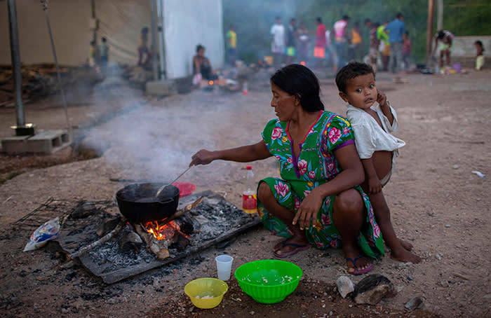 TOPSHOT - Members of the Warao tribe, Venezuela's second-largest indigenous group, prepare food at the Janokoida shelter where they have been taking refuge in the border city of Pacaraima, Roraima State, Brazil, on August 21, 2018. - Desperate Venezuelans fleeing the country's crisis continue to cross the Brazilian border, despite the violent anti-migrant riot that took place last week in the border town of Pacaraima. (Photo by Mauro PIMENTEL / AFP)MAURO PIMENTEL/AFP/Getty Images
