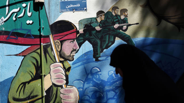 An Iranian woman walks past murals of Iranian soldiers marching during the Iran-Iraq war (1980-88), on May 8, 2015, on Palestine square in Tehran, after a demonstration to denounce the strikes by the Saudi led coalition against the Shiite rebellion in Yemen, where Iran is accused of meddling by Riyadh. AFP PHOTO / BEHROUZ MEHRI (Photo credit should read BEHROUZ MEHRI/AFP/Getty Images)