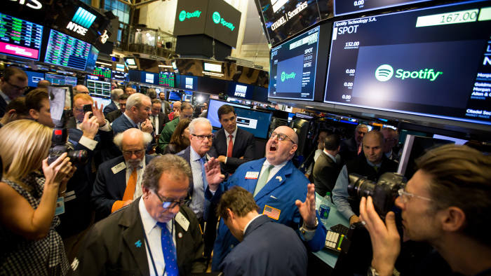 Traders work during the first day of trading for Spotify Technology SA on the floor of the New York Stock Exchange (NYSE) in New York, U.S., on Tuesday, April 3, 2018. Spotify shares climbed in the minutes after it began trading through a direct listing. The company skipped the traditional initial public offering process in favor of a route rarely taken by large, established companies. Photographer: Michael Nagle/Bloomberg