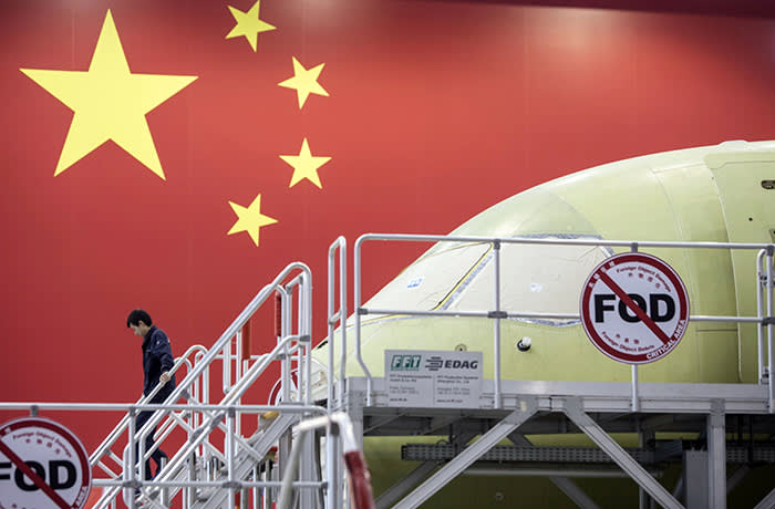 A Chinese national flag hangs over a Commercial Aircraft Corp. of China Ltd. (Comac) C919 being assembled at the Comac Shanghai Research and Development Center in Shanghai, China on Thursday May 4, 2017. China's first modern passenger jet took off on its first test flight on May 5, giving wings to President Xi Jinping's ambition to make China an advanced economy. Photographer: Qilai Shen / Bloomberg