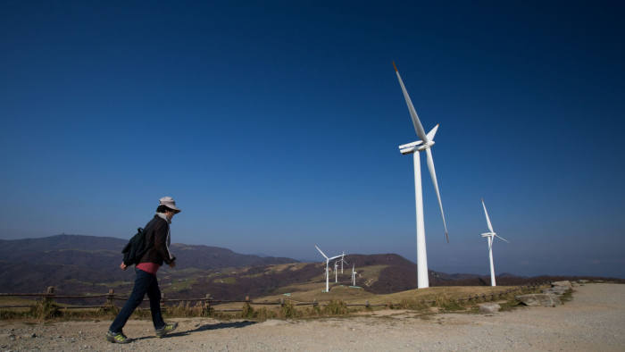A woman walks toward wind turbines, manufactured by Vestas Wind Systems A/S and Unison Co., standing at Daegwanryeong Samyang Ranch in Pyeongchang, South Korea, on Friday, Nov. 1, 2013. South Korea wants a broader energy mix as it seeks to solve recurring supply shortages in Asia's fourth-largest economy, the country's energy minister said in October. Photographer: SeongJoon Cho/Bloomberg