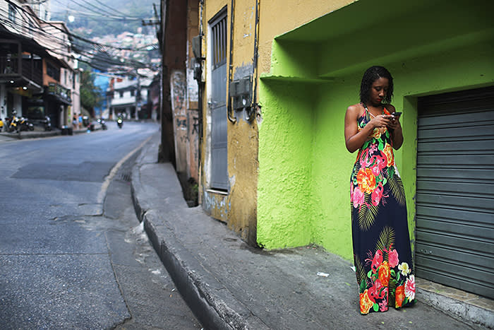 RIO DE JANEIRO, BRAZIL - SEPTEMBER 24: A woman checks her phone in the Rocinha 'favela' community on September 24, 2017 in Rio de Janeiro, Brazil. The Brazilian Army and other armed forces entered the favela September 22 in an ongoing operation following firefights involving drug gangs in the favela, which is one of the largest in Latin America. Rio has suffered an uptick in violence following the Rio 2016 Olympic Games. (Photo by Mario Tama/Getty Images)