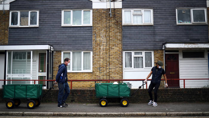 Volunteers cart food donations from a local food bank through the Carpenters Estate in Stratford, as the spread of the coronavirus disease (COVID-19) continues, in east London, Britain, March 31, 2020. Picture taken March 31. REUTERS/Hannah McKay TPX IMAGES OF THE DAY
