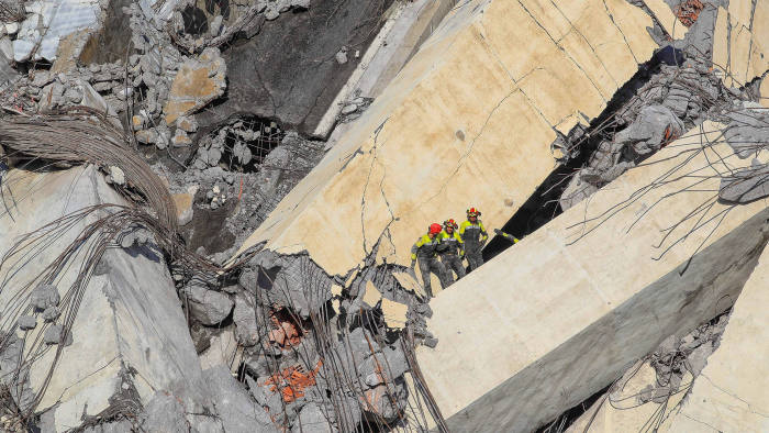 TOPSHOT - Italian rescuers climb onto the rubble of the collapsed Morandi motorway bridge to look for victims and survivors in the northern port city of Genoa on August 14, 2018. - At least 30 people were killed on August 14 when the giant motorway bridge collapsed in Genoa in northwestern Italy. The collapse of the viaduct, which saw a vast stretch of the A10 freeway tumble on to railway lines in the northern port city, was the deadliest bridge failure in Italy for years, and the country's deputy transport minister warned the death toll could climb further. (Photo by Valery HACHE / AFP) (Photo credit should read VALERY HACHE/AFP/Getty Images)