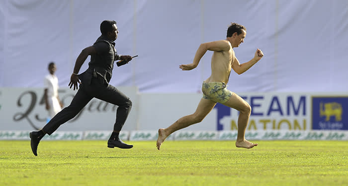 A streaker runs as a police officer attempts to catch him during the fourth day of the first test cricket match between Sri Lanka and England in Galle, Sri Lanka, Friday, Nov. 9, 2018. (AP Photo/Eranga Jayawardena)