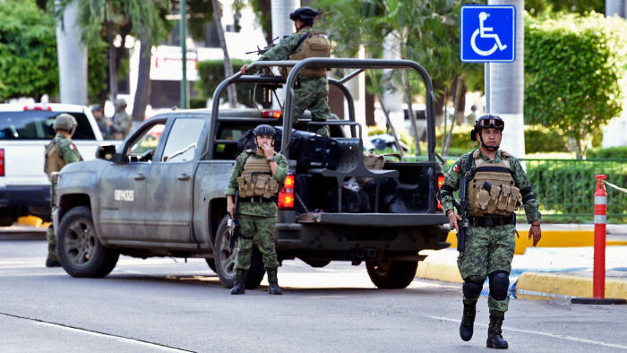 """Soldiers patrol the surroundings of the government palace in Culiacan, Sinaloa state, Mexico, on October 18, 2019. - Mexico's president faced a firestorm of criticism Friday as his security forces confirmed they arrested kingpin Joaquin """"El Chapo"""" Guzman's son, then released him when his cartel responded with an all-out gun battle. (Photo by ALFREDO ESTRELLA / AFP) (Photo by ALFREDO ESTRELLA/AFP via Getty Images)"""