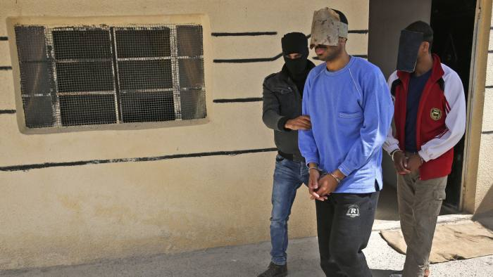 FILE- In this file photo dated Friday, March 30, 2018, a Kurdish security officer escorts Alexanda Kotey, left, and El Shafee Elsheikh, who were allegedly among four British jihadis who made up a brutal Islamic State cell dubbed