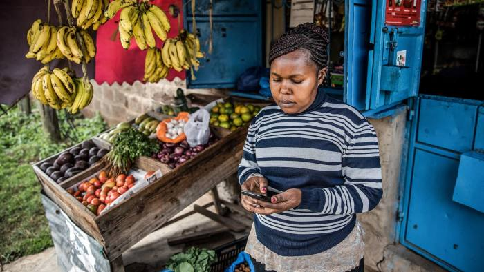 Janeffer Wacheke, co-owner of a fresh-vegetable stall, checks her mobile phone for a purchase order of vegetables and fruits made to Twiga Foods Ltd., while on her stall in Nairobi, Kenya, on June 11, 2018. Wacheke's fresh-vegetable stall in Nairobi uses technology that's helping crack a problemKenyanbanks have so far failed to solve -- measuring the creditworthiness of traders in the country's $20 billion informal economy. Photographer: Luis Tato/Bloomberg