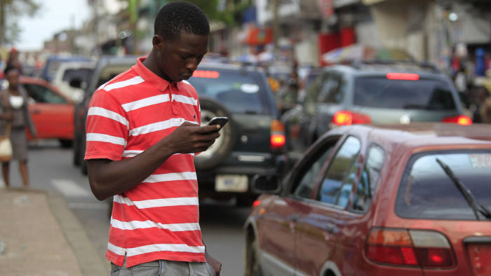 epa05267151 A photograph made available 19 April 2016 shows a man using a cellphone in Monrovia, Liberia 18 April 2016. The mobile industry in West Africa has grown from a state controlled space to becoming a massive market fueling economic growth and technological innovation. Mobile network operators have stiff competion between each other for the millions of African consumers looking to connect in an easy and affordable way. The cellphone industry has in many instances circumvented the problematic fixed line infrastructure of existing telecommunications networks. Proponents to this growth in mobile technology include a World Bank investment of $50 million USD in infrastructure development and capacity building as well as a fiber optic submarine West African Cable System (WACS) aimed at dramatically increase broadband capacity for the region. EPA/AHMED JALLANZO