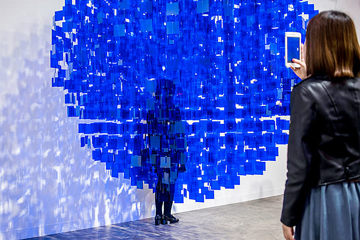"A woman poses for a photograph behind artist Julio Le Parc's ""Sphère bleue"" at Art Basel in Hong Kong on March 29, 2018. / AFP PHOTO / Philip FONG / RESTRICTED TO EDITORIAL USE - MANDATORY MENTION OF THE ARTIST UPON PUBLICATION - TO ILLUSTRATE THE EVENT AS SPECIFIED IN THE CAPTION (Photo credit should read PHILIP FONG/AFP/Getty Images)"