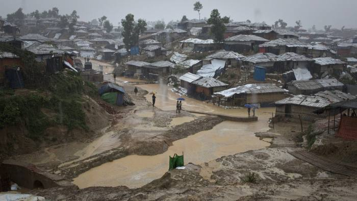 Rohingya refugees shield from the rain in Balukhali, Camp 10, part of the mega refugee camp sheltering over 800,000 Rohingya refugees, Cox's Bazar, Bangladesh, June 12, 2018. The biggest refugee camp in the world is battling the onset of the monsoon rains. Humanitarian organisations on the ground and the Bangladeshi government are working hard to minimise the risks from landslides, flash floods, water born diseases and ultimately, loss of life. Thousands are facing dire circumstances as the conditions in the camps are expected to dramatically worsen with the onset of the heavy rains.