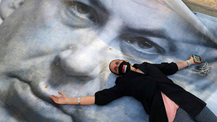 "TOPSHOT - An Israeli woman wearing a face mask with "" crime minister"" written on it, lies on a banner during a ""Black Flag"" demonstration, to protest against Prime Minister Benjamin Netanyahu (image) and anti-democratic measures to contain the novel coronavirus outbreak, at Rabin Square in the coastal city of Tel Aviv, on April 19, 2020. (Photo by JACK GUEZ / AFP) (Photo by JACK GUEZ/AFP via Getty Images)"