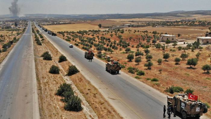 TOPSHOT - A convoy of Turkish military vehicles is pictured near the town of Maar Hitat as smoke billows in the background, during reported air strikes by pro-regime forces in northern Syria's Idlib province on August 19, 2019. - A Turkish military convoy crossed into northwest Syria today, heading towards a key town where regime forces are waging fierce battles with jihadists and rebels. (Photo by Omar HAJ KADOUR / AFP)OMAR HAJ KADOUR/AFP/Getty Images