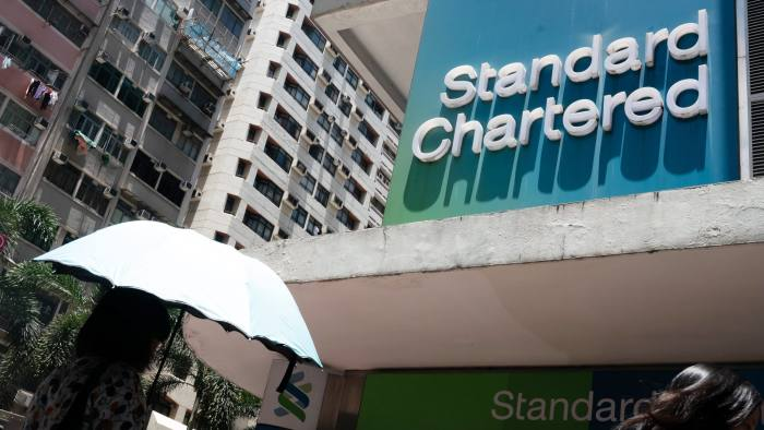 Pedestrians walk past a Standard Chartered Plc bank branch in Hong Kong, China, on Tuesday, July 31, 2018. Standard Chartered, one of the biggest financiers of global trade, isn't losing sleep over an increasingly fractious relationship between the world's two largest economies. Photographer: Anthony Kwan/Bloomberg