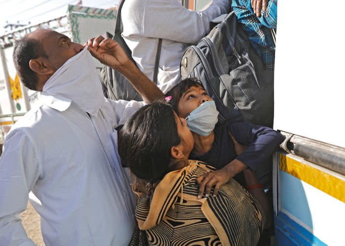 On the outskirts of New Delhi on March 29, a woman pushes her daughter on to an overcrowded bus as they attempt the journey back to their home village
