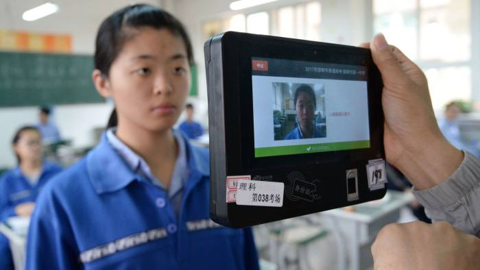 A teacher uses a machine which employs both fingerprint and facial recognition technology to check the identification of a student before a simulated college entrance exam in Handan in China's northern Hebei province on June 6, 2017. The simulated exam was held to familiarise students with the process to be used for annual college entrance exams which begin nationwide on June 7. Millions of students across China will take the exams. / AFP PHOTO / STR / China OUTSTR/AFP/Getty Images