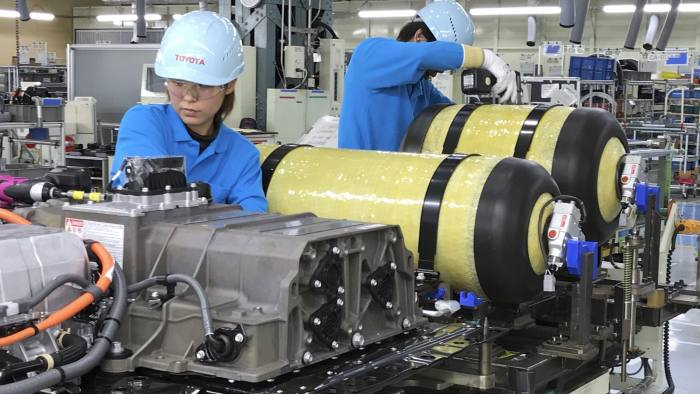 """In this Oct. 30, 2017, photo, workers of Toyota Motor Corp. set hydrogen-stored tanks, in yellow, to be placed into a Mirai fuel cell vehicle at the automaker's Motomachi plant, in Toyota, western Japan. Toyota is banking on a futuristic """"electrification"""" auto technology called hydrogen fuel cells for its zero-emissions option. The Associated Press got a tour of Toyota's Motomachi plant that assembles the Mirai fuel cell vehicle. (AP Photo/Yuri Kageyama)"""