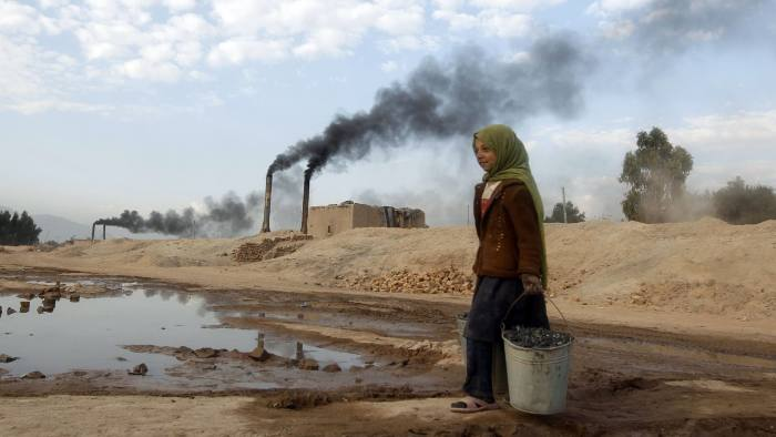 Aisha carries coal to be used for cooking and heating from a brick-making factory in Jalalabad...Aisha 11, carries coal to be used for cooking and heating from a brick-making factory in Jalalabad December 17, 2013. REUTERS/Parwiz (AFGHANISTAN - Tags: SOCIETY)