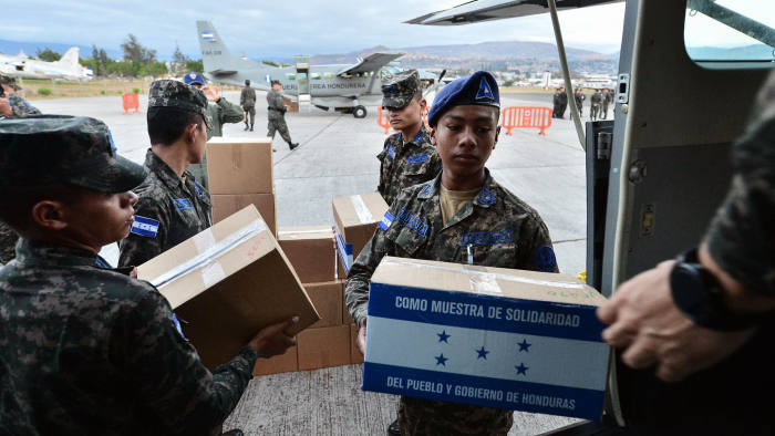 Honduran Air Force soldiers load humanitarian aid for Venezuela on an aircraft at Hernan Acosta Mejia air base, in Tegucigalpa, on March 01, 2019. - Three Cessna 208B recently donated by the US government to Honduras, headad to Cucuta, in the Colombian border with Venezuela, loaded with humanitarian aid to be delivered for its distribution to Venezuelan opposition leader and self-declared acting president Juan Guaido's representatives. (Photo by ORLANDO SIERRA / AFP) (Photo credit should read ORLANDO SIERRA/AFP/Getty Images)